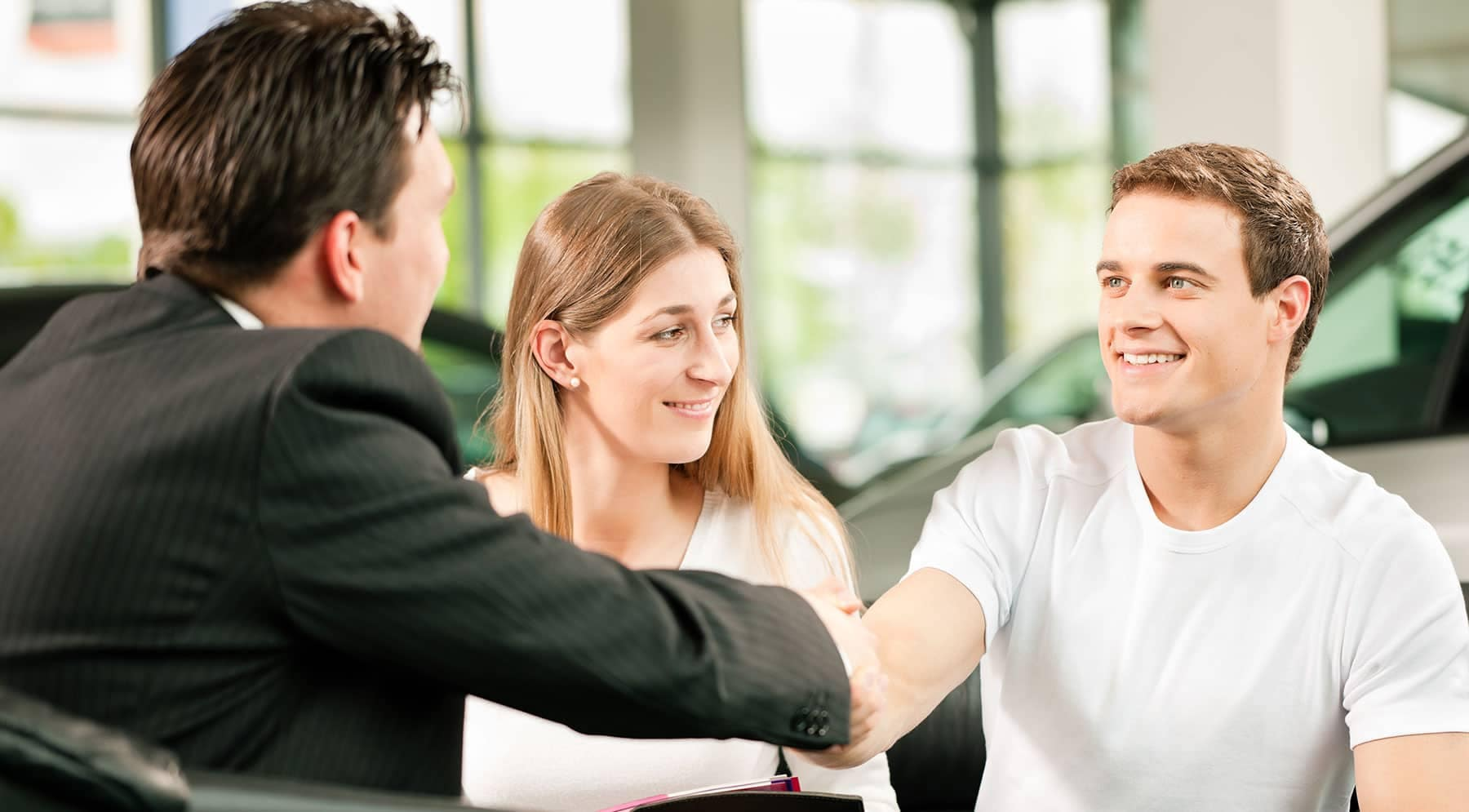 young man and woman shaking hands with a salesman