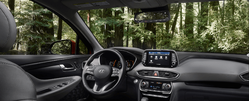 2020 Hyundai Santa Fe interior steering wheel and dashboard looking out on forest