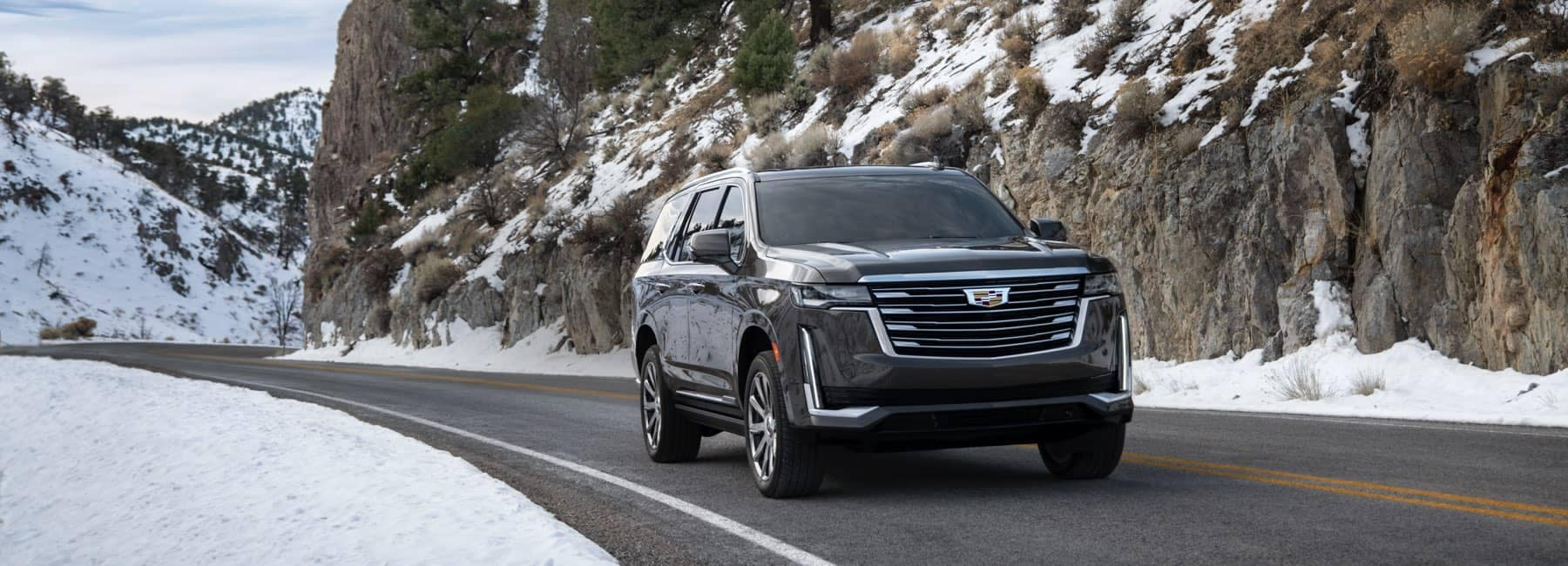 2021 Cadillac Excalade driving down a snowy road