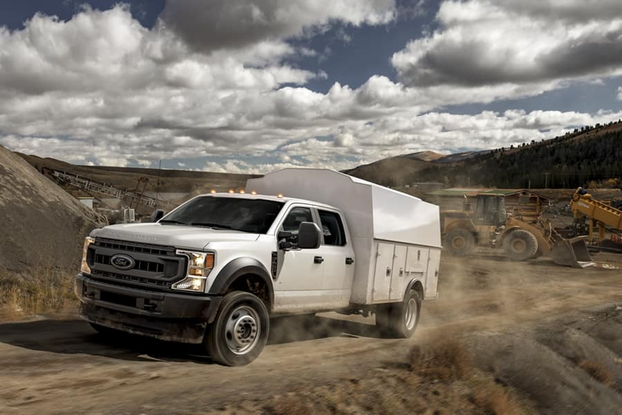 Ford commercial truck with upfit driving up a dirt road.