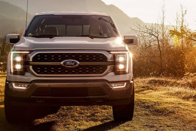 A silver 2021 Ford F150 parked in on a wooded trail at sunset_mobile