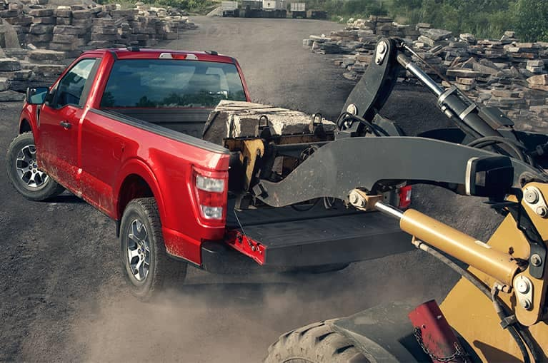 Red 2021 Ford F-150 hauling construction equipment