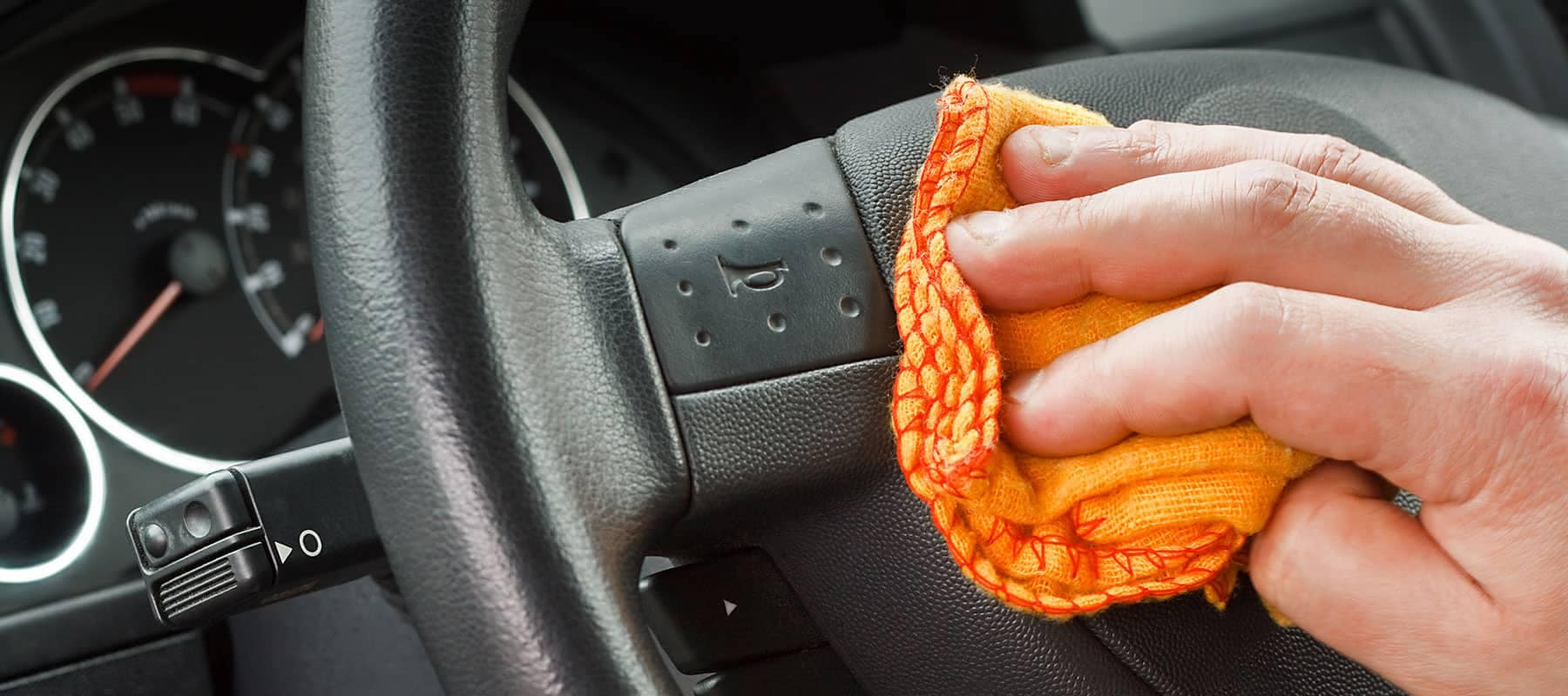hand wiping down steering wheel