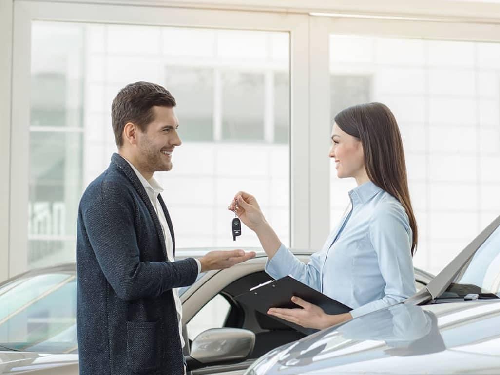 saleswoman is handing car keys to man inside showroom