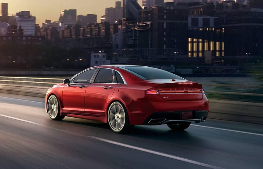 2020 Lincoln MKZ in the Red Carpet exterior color is shown being driven along a highway and into the sunset