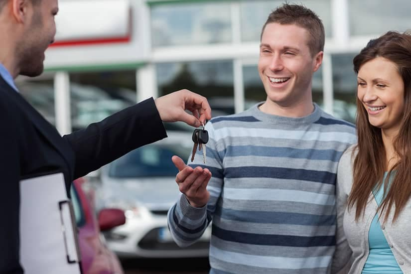 Couple receiving new car keys