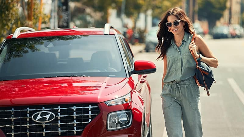 red Hyundai parked on road with smiling woman