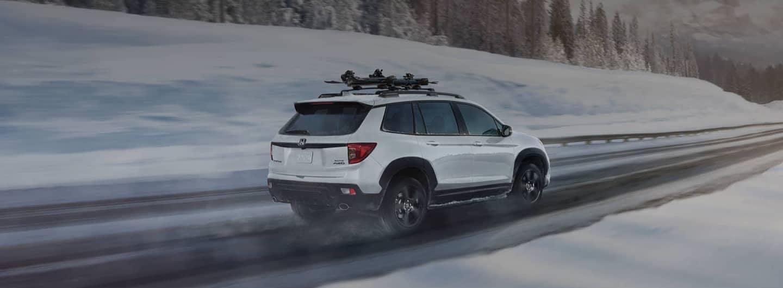 Honda driving along snowy mountain road