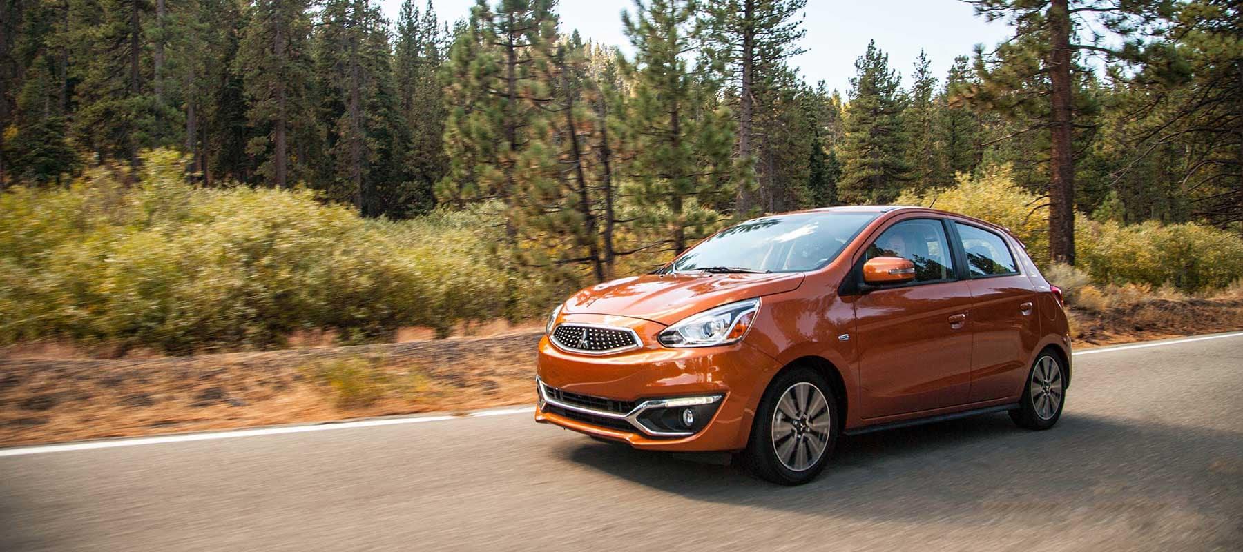 2019-Orange-Mitsubishi-Mirage driving through a forest road