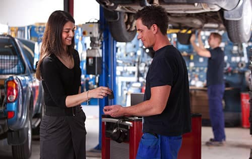 woman is handing her car keys to a service technician