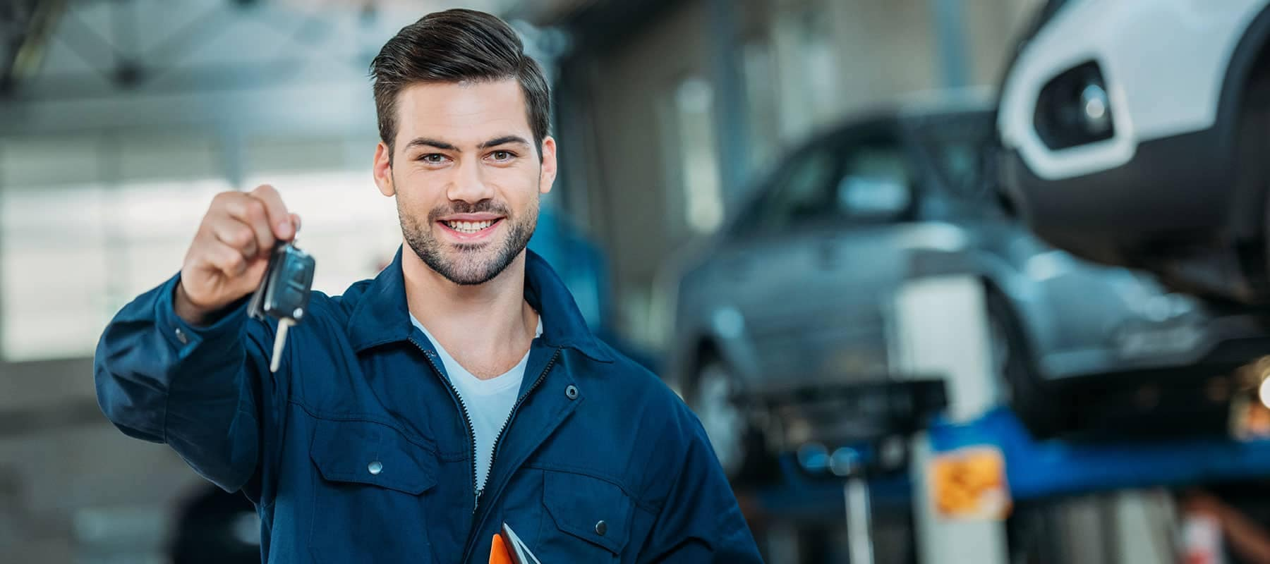 Service picture of technician holding car keys out and smiling