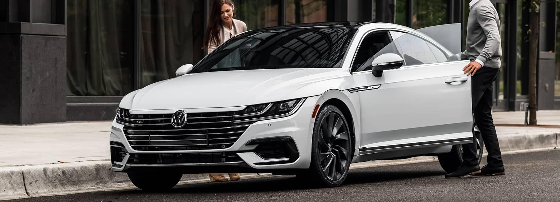 2020 VW White Arteon parked in city with a man and woman climbing inside