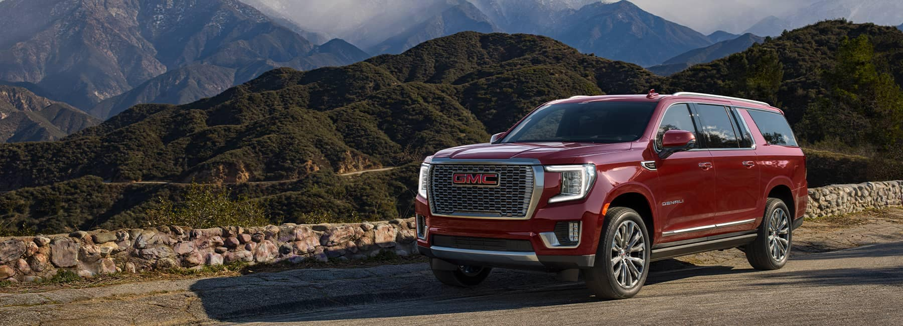 2021 Cayenne Red Yukon XL Denali in front of a mountain