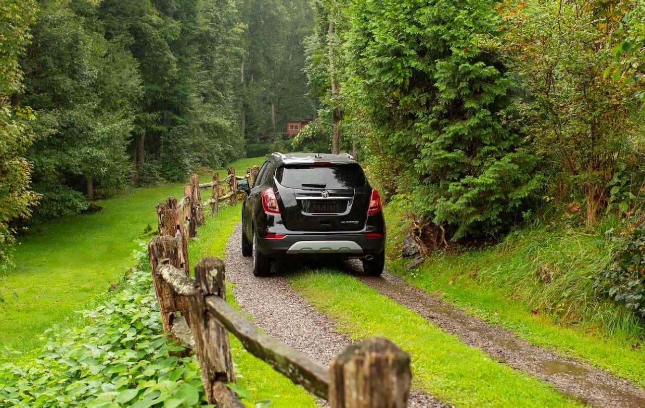 GM SUV Driving down grassy road