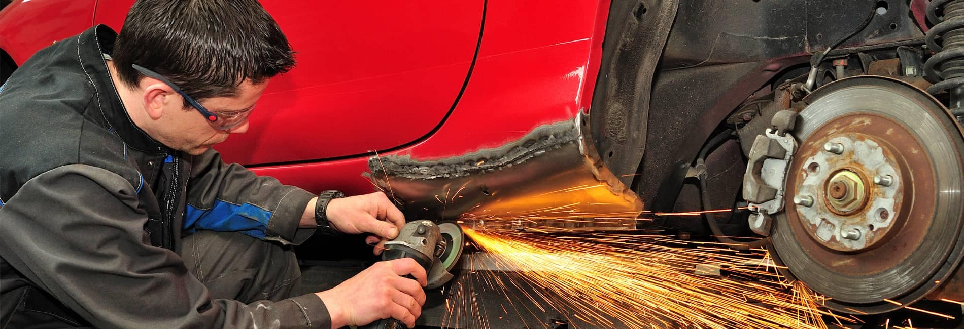 service technician working on car repair with sparks from grinder