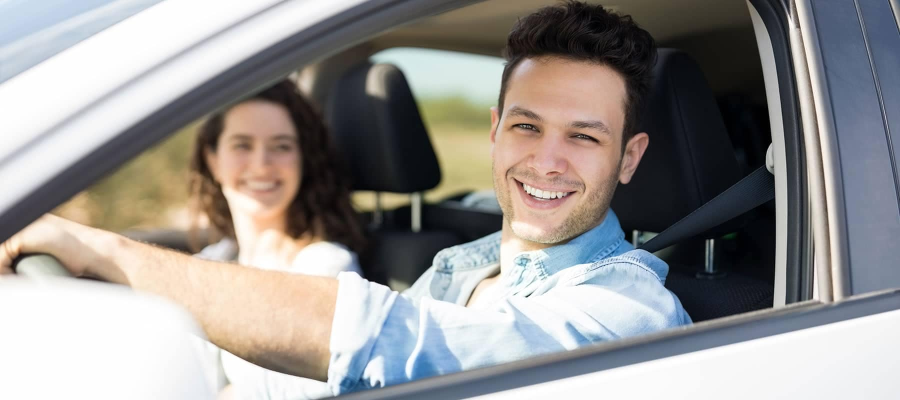 smiling man and woman in car