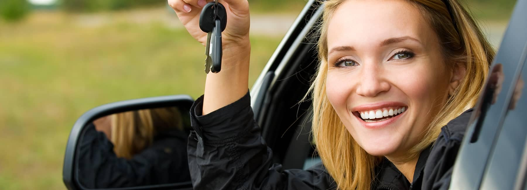 woman leaning out of car smiling with her car keys