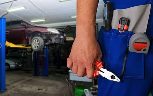 Mechanic holding a wrench in front of raised car