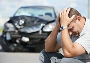 guy in front of a smashed car