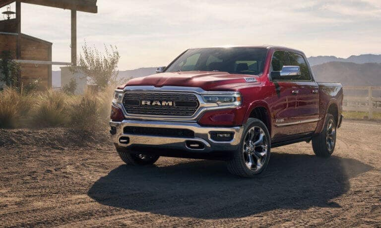 A red 2019 Ram 1500 driving on a farm