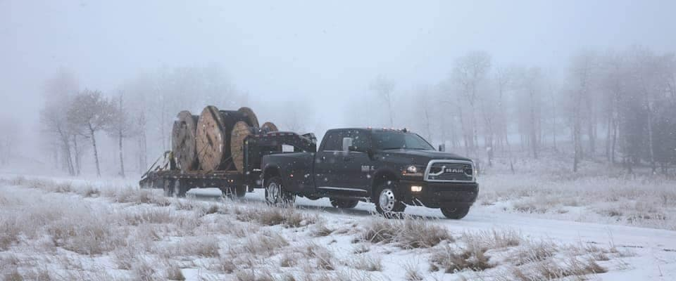 a black Ram 2500 towing equipment on a snowy day