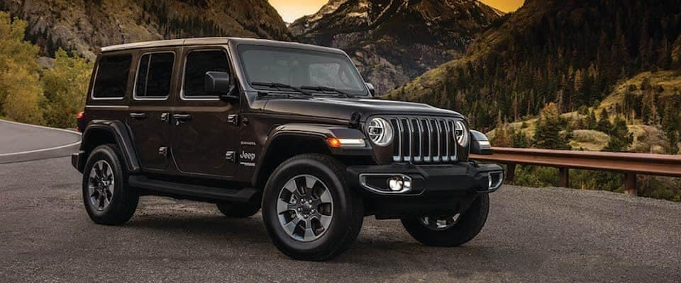 A 2019 Jeep Wrangler parked in front of the mountains at sunset