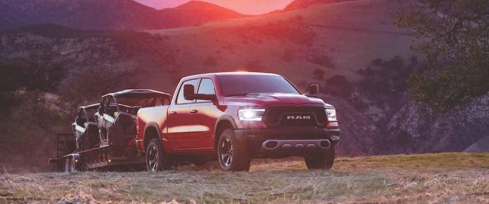 A red 2019 Ram 1500 towing two atvs at sunset