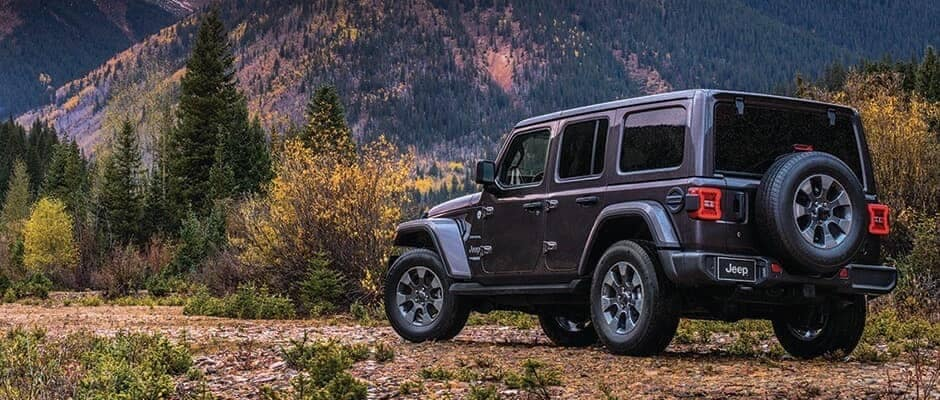 A 2019 Jeep Wrangler parked in front of mountains at sunrise
