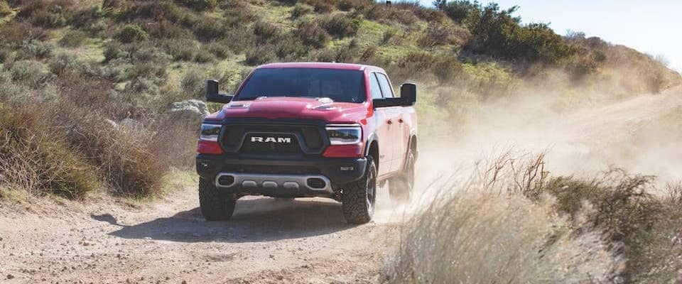 A red 2019 Ram 1500 driving down a dirt road