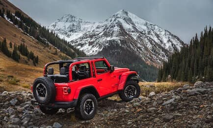 A red Jeep Wrangler parked in the mountains
