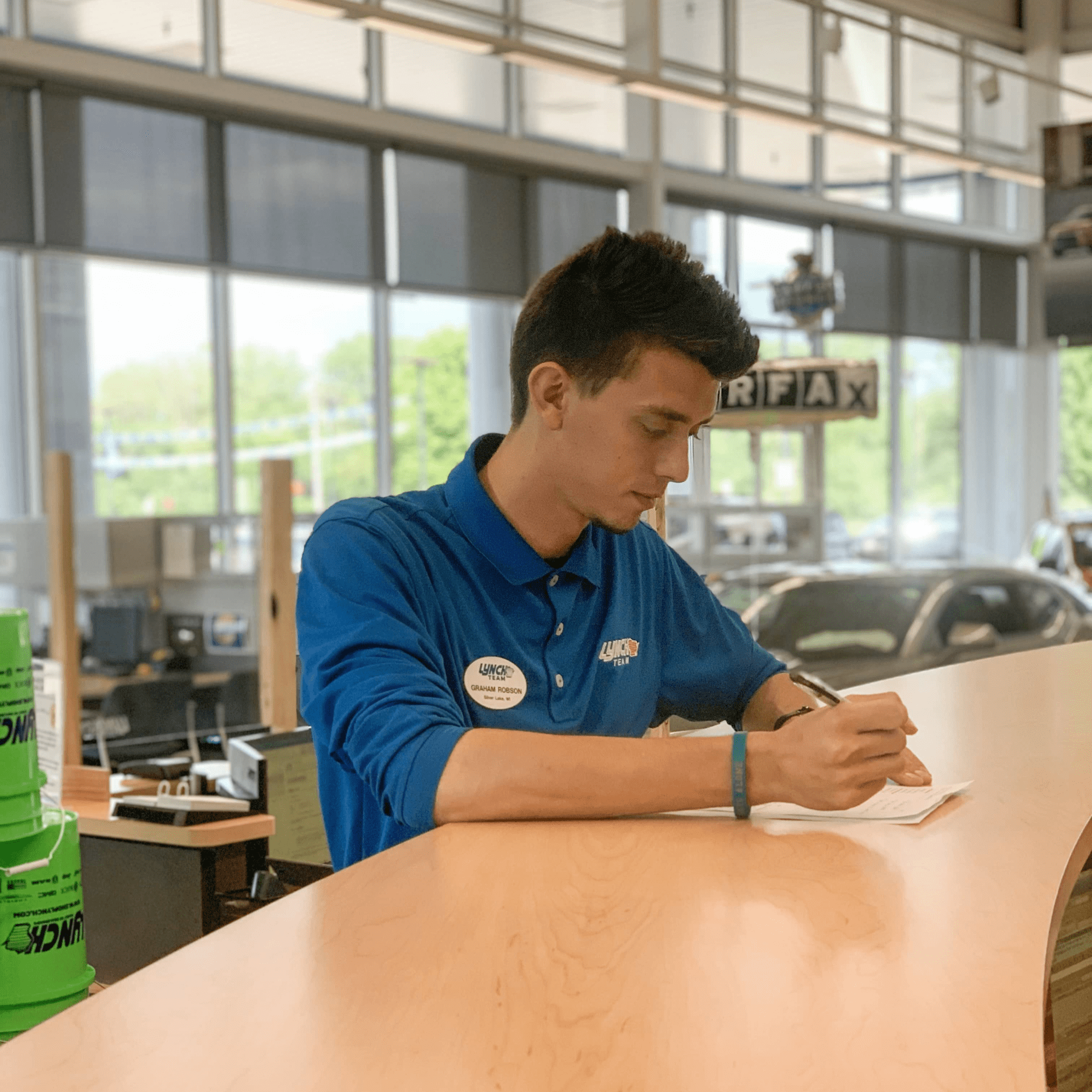 Car salesman fills out form at counter