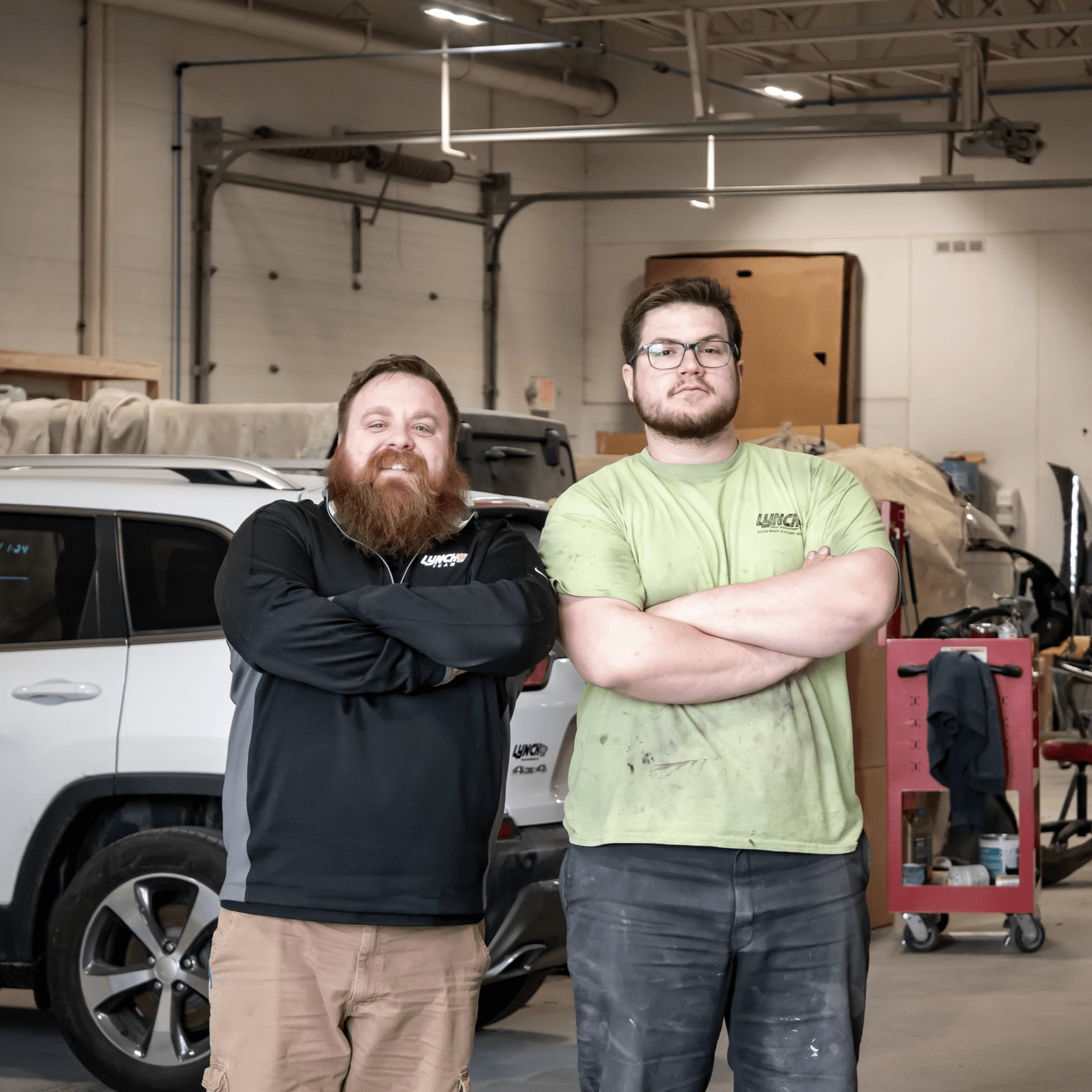Two technicians stand with folded arms in service garage