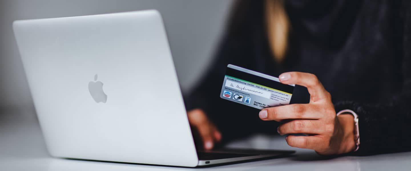 Person on laptop holding credit card