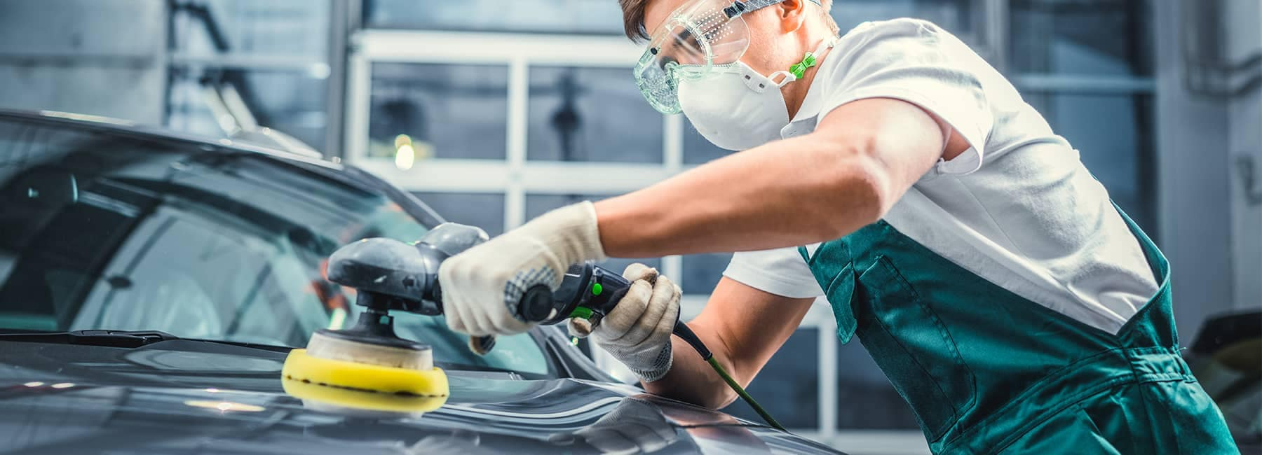 Mechanic buffing the paint of a car at an auto body shop