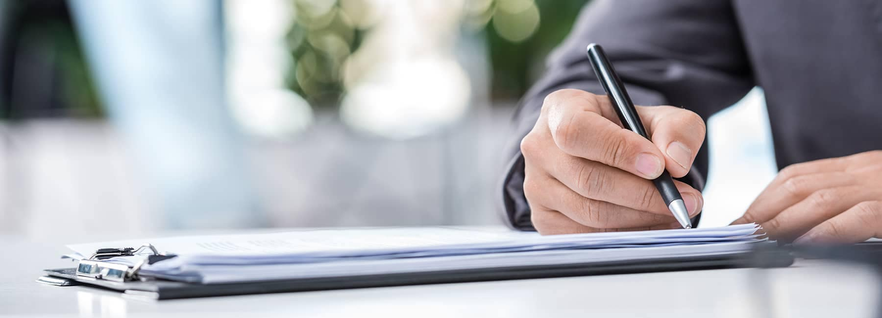 man signing finance papers