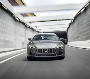 A silver Maserati Ghibli racing through a well lit tunnel at night