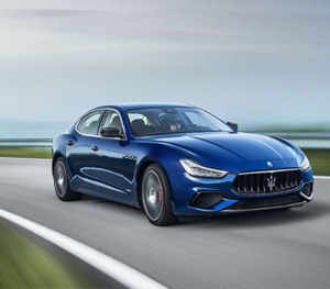 A blue Maserati Ghibli racing along a European style racetrack - the road and grass look very nice