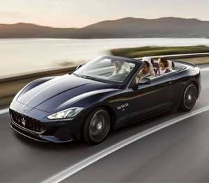 Three people in a black Maserati GranCabrio drive swiftly along a one lane highway with the sunset glimmering off the lake in the background