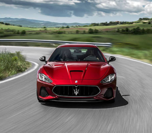 A red Maserati GranTurismo races along a curve country highway on a beautiful summer day