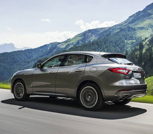 A grey Maserati Levante rolls along a highway with a picturesque mountain landscape in the background