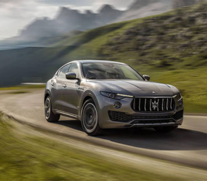 A dark grey Maserati Levante cruises along a highway with a very rocky mountain landscape in the background