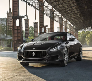 A black Maserati Quattroporte is parked in an abandoned looking building in a unknown urban area