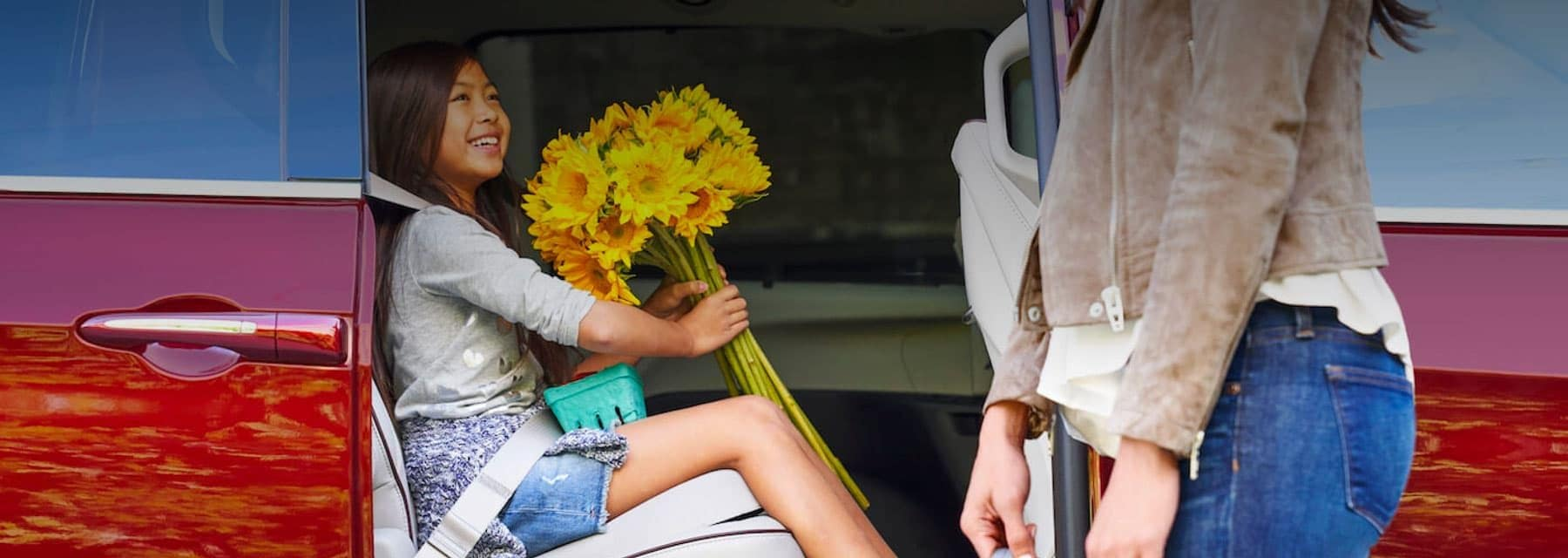 Young girl holding a bundle of yellow sun flowers in her hands while sitting in the back of a red Chrysler Pacifica