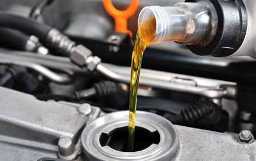 oil pouring into car engine
