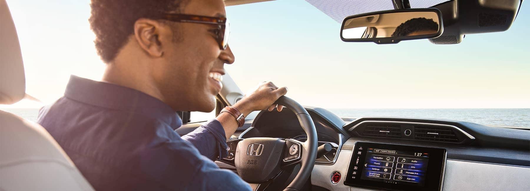 Smiling man drives Honda Clarity