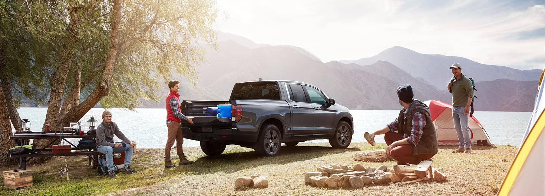 Men are camping with their Honda Ridgeline alongside a lake