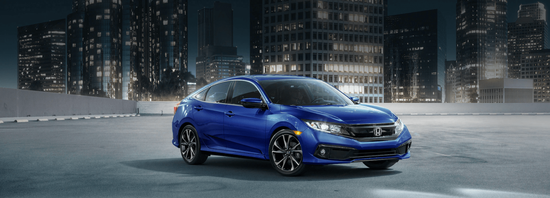 2021-Honda-Civic-Sedan-in-an-empty-parking-lot-in-front-of-an-urban-cityscape-at-night