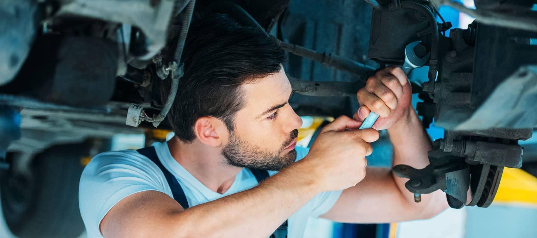 service technician loosens bolt on car undercarriage