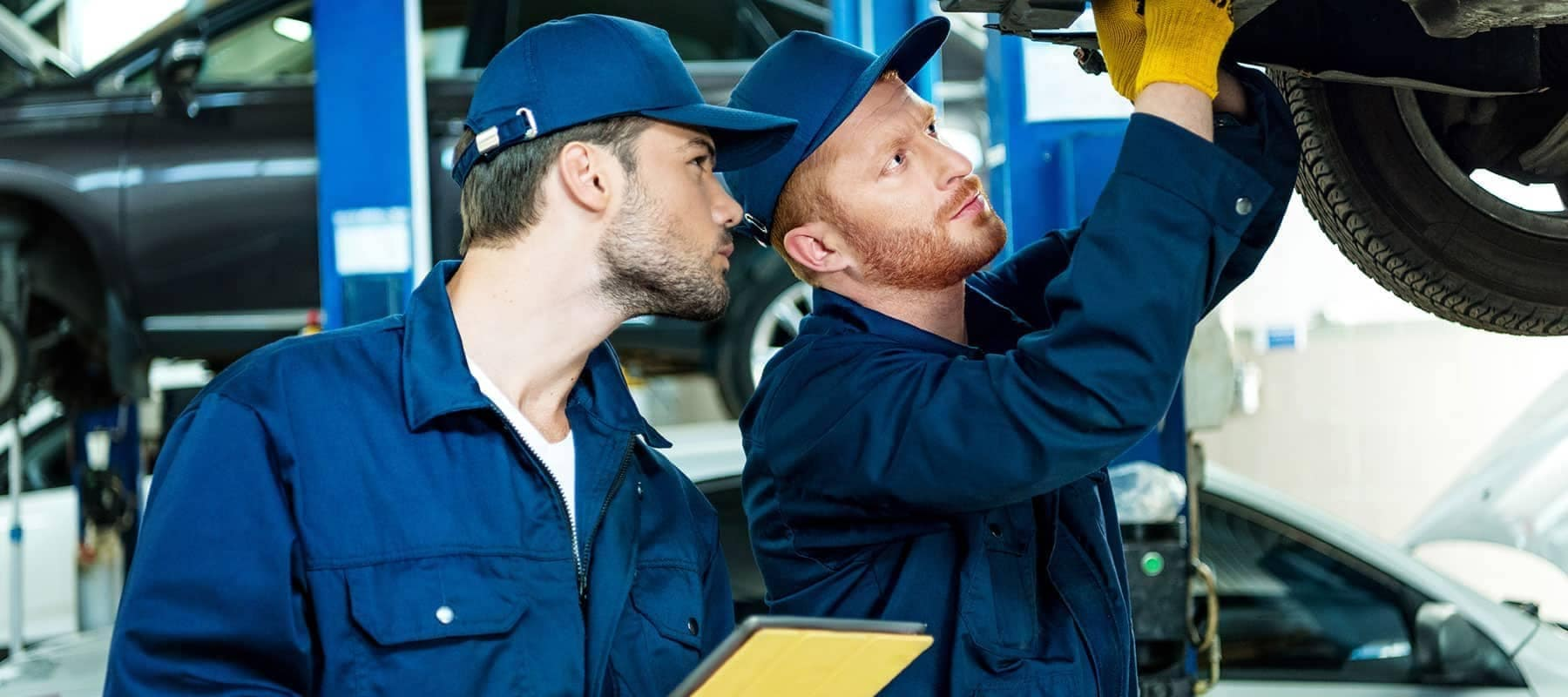 Two-Mechanics make repairs to undercarriage of vehicle