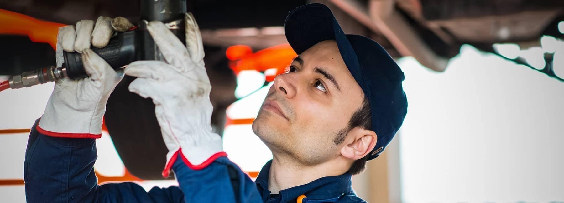technician repairing under car